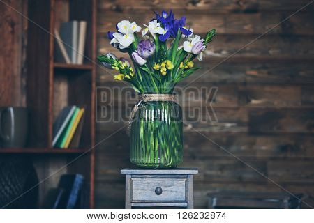 A bouquet of fresh flowers in a glass vase on wooden background