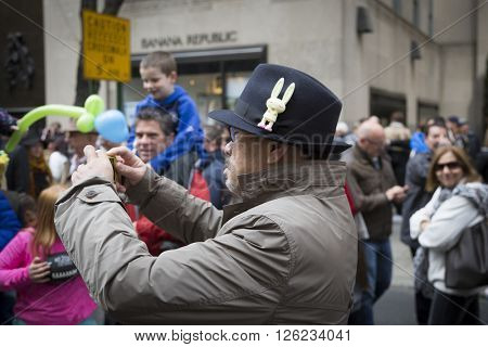 NEW YORK - MAR 27 2016: A man wearing a hat with an Easter Bunny on it takes pictures of parade goers on 5th Ave Easter Sunday at the traditional Easter Bonnet Parade in Manhattan on March 27, 2016.