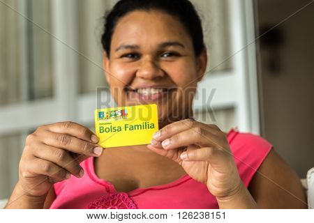 SAO PAULO, BRAZIL - CIRCA APRIL, 2016: Illustrative editorial of a woman showing Bolsa Familia Card. Bolsa Familia is a social welfare program of the Brazilian government, part of the Fome Zero
