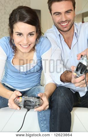 Young man and young woman playing video game