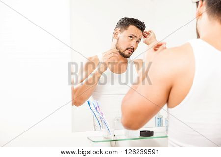 Attractive Man Combing His Hair In The Bathroom