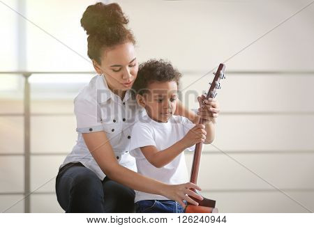 Young girl and little boy with a guitar