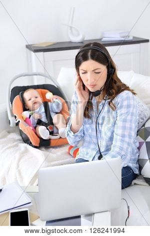 Beautiful woman with baby boy working from home using laptop and headset