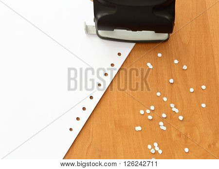 Hole puncher with paper on the office table