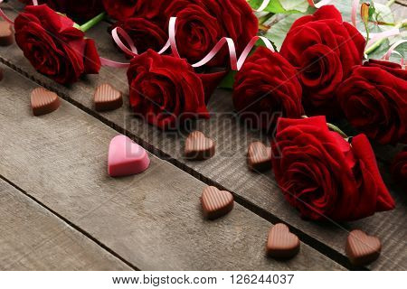 Bouquet of beautiful red roses with small hearts on wooden table closeup