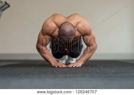 Young Bodybuilder Exercising Press Ups On Floor