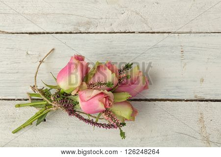Pastel pink roses as a still life on a grunge textured wooden table