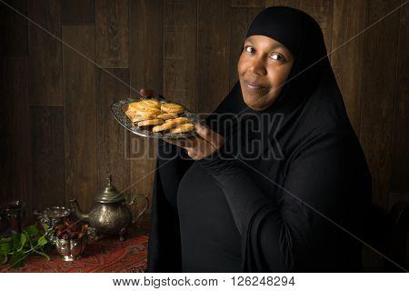 Friendly African muslim woman presenting traditional cookies