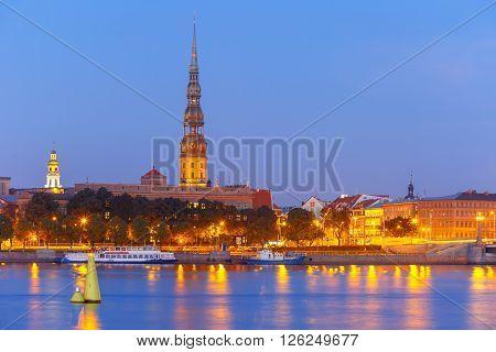 Saint Peter church, Stone Bridge and River Daugava in the Old Town of Riga at night, Latvia