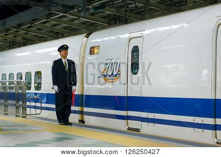 OSAKA JAPAN - NOVEMBER 24 2015: Unidentified Japanese train conductor on his duty on a Shinkansen platform at Kyoto Station