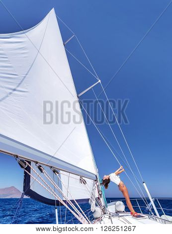 Happy joyful woman having fun on sailboat, spending summer vacation on the sea, enjoying freedom and active holidays
