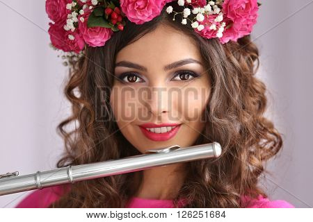 Portrait of beautiful young woman with flute closeup