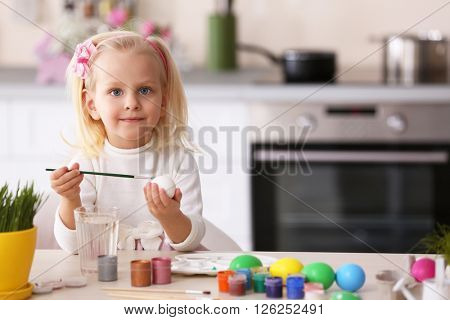 Little girl painting Easter eggs in the kitchen