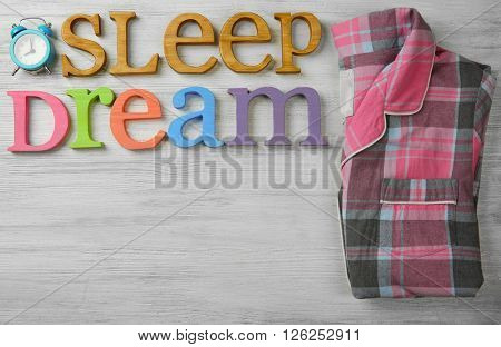 Text SLEEP DREAM, pajamas and alarm clock on wooden table, top view