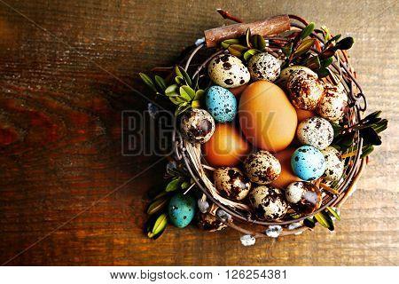 Bird eggs in wicker basket on  wooden background . Retro stylization