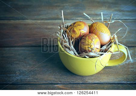 Easter eggs in mug on wooden background. Retro stylization