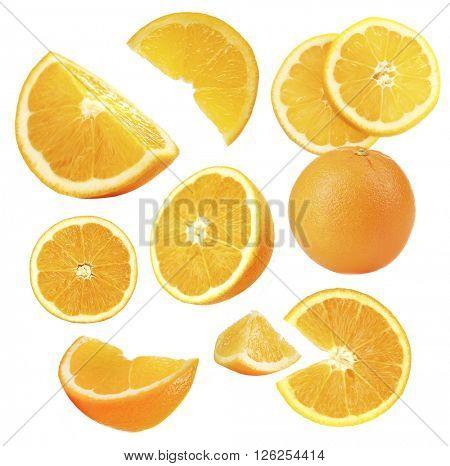 Falling ripe oranges isolated on white