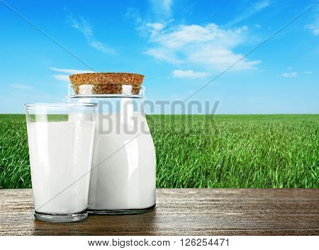 Jar, glass of milk on wooden table against green field and blue sky background