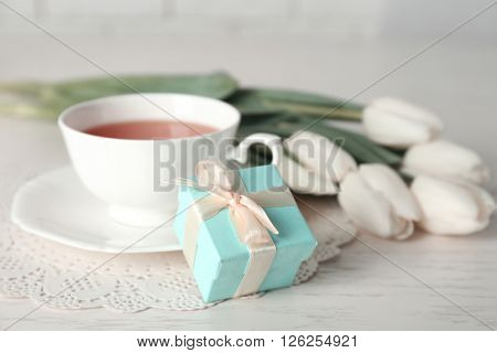 Present box with tulips and cup of tea on wooden table closeup