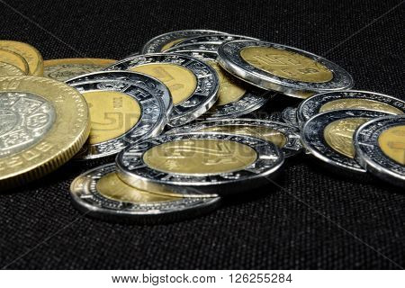 pesos coins in different denominations in a pile from 1 to 15 pesos.
