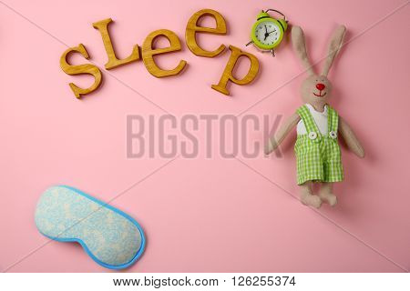Word SLEEP, mask, alarm clock and toy rabbit on pink background