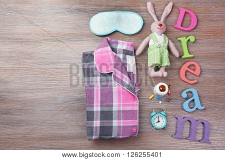 Word Dream with little toy, pajamas and mask on a wooden background