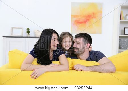 Parents and their daughter sitting on the back of yellow sofa.