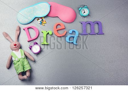 Word Dream with pills, sleeping masks and little toy  on a grey background