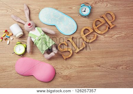 Word Sleep with pills, sleeping mask and little toy  on a wooden background