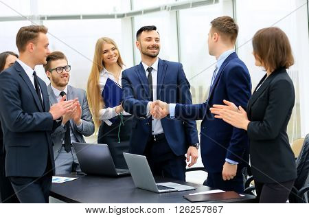 Group of confident business people in formal wear sitting at the table together and smiling while two men handshaking