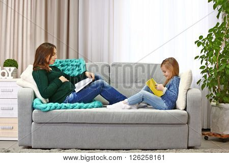 Pregnant woman and her child reading books on couch