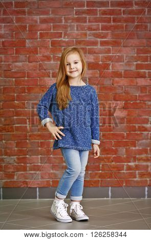 Beautiful small girl against brick wall background