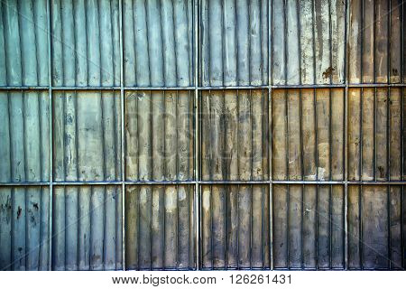 Rusty oxidized aluminum metal platted garage wall metallic surface texture with horizontal and vertical reinforcing bars as background.