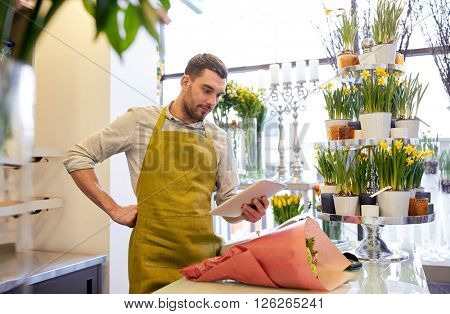people, business, technology, sale and floristry and concept - happy smiling florist man with tablet pc computer at flower shop counter