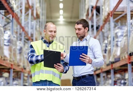 wholesale, logistic, people and export concept - manual worker and businessmen with clipboards at warehouse