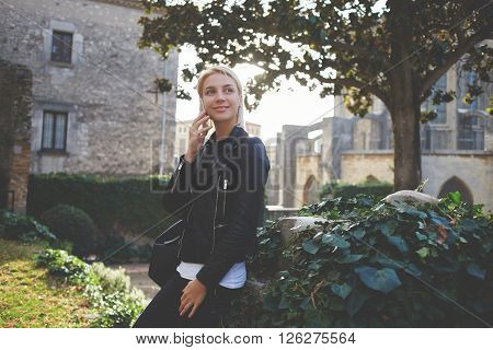 Happy smiling female student having mobile phone conversation with her boyfriend during break between lectures in university. Hipster girl in good mood is phoning via cell telephone during spare time