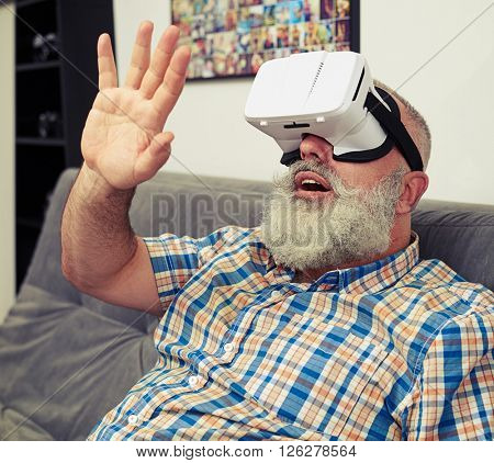 Senior Caucasian man rising his hand and trying to touch something using virtual reality headset glasses