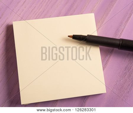 Blank paper with pen on purple color painted wooden table