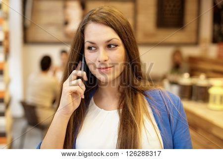 Closeup portrait of young woman talking on mobilephone, looking away.