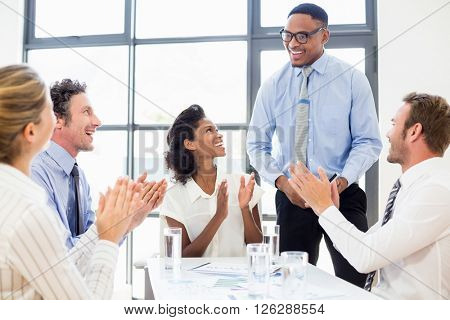 Business team applauding a colleague in meeting