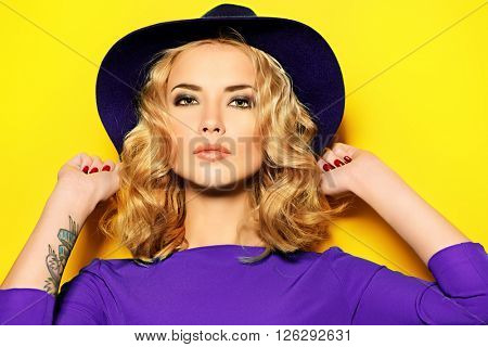 Bright fashion concept.  Beautiful girl with curly blonde hair wearing purple dress posing over yellow background.