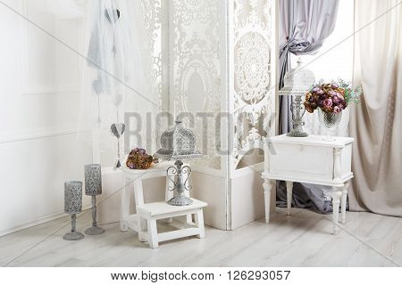 shabby chic room interior. Wedding decor, room decorated for shabby chic rustic wedding, with bedside table, folding screen or room divider with white tracery and rose bouquets. High key poster