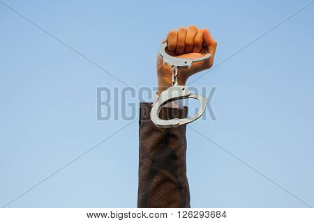 Business man showing handcuffs after releasing it. Financial freedom or business criminal concept.