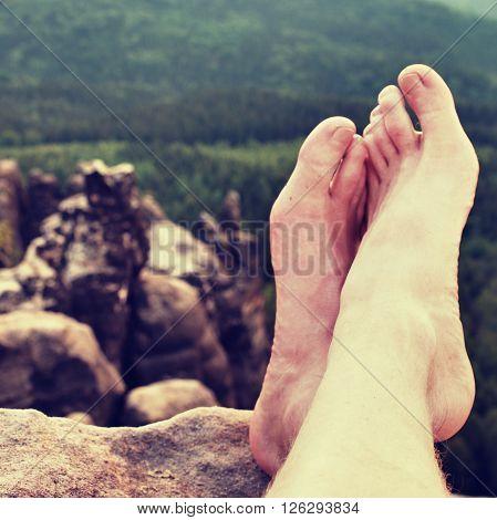 Naked Male Sweaty Long Legs On Peak Of Sharp Rock Above Valley.
