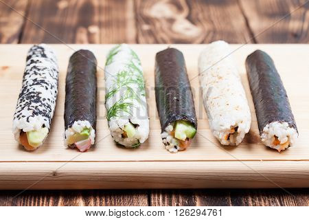 Homemade sushi rolls on wooden cutting board