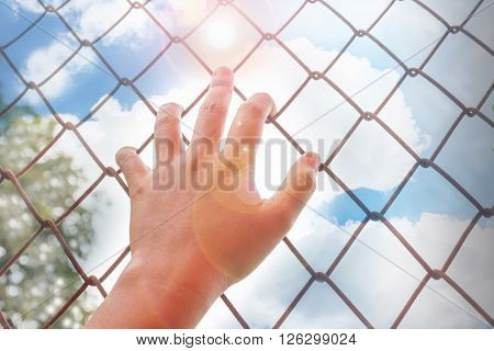 Women hand catching rysty iron bar with tree and wide blue sunny sky background and copy space freedom desire concept
