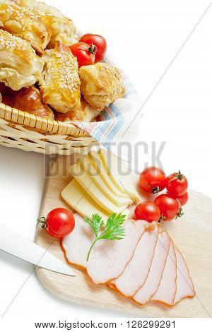 Freshly baked puff pastry patties sprinkled with sesame seeds in a wicker basket closeup arranged with cherry tomatoes cheese ham parsley and kitchen knife isolated on white background.