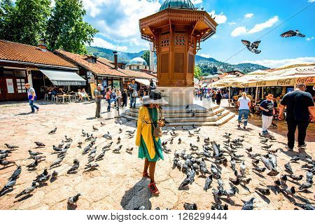 SARAJEVO, BOSNIA - HERZOGOVINA - CIRCA JUNE 2015: Crowded old market squire with pigeons and Sebilj fontain on the north bank of the river Miljacka in the municipality of Stari Grad in Sarajevo.