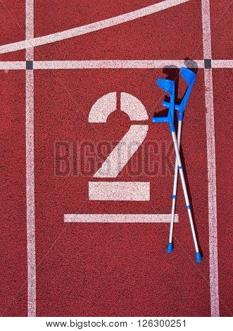 Medicine Crutch At Number Two. Big White Track Number On Red Rubber Racetrack. Gentle Textured Runni