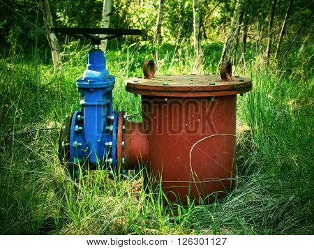Old expansion pipe of drink water pipes joined with new blue valve and new blue joint members. New dump valve. Metal corroded texture. poster